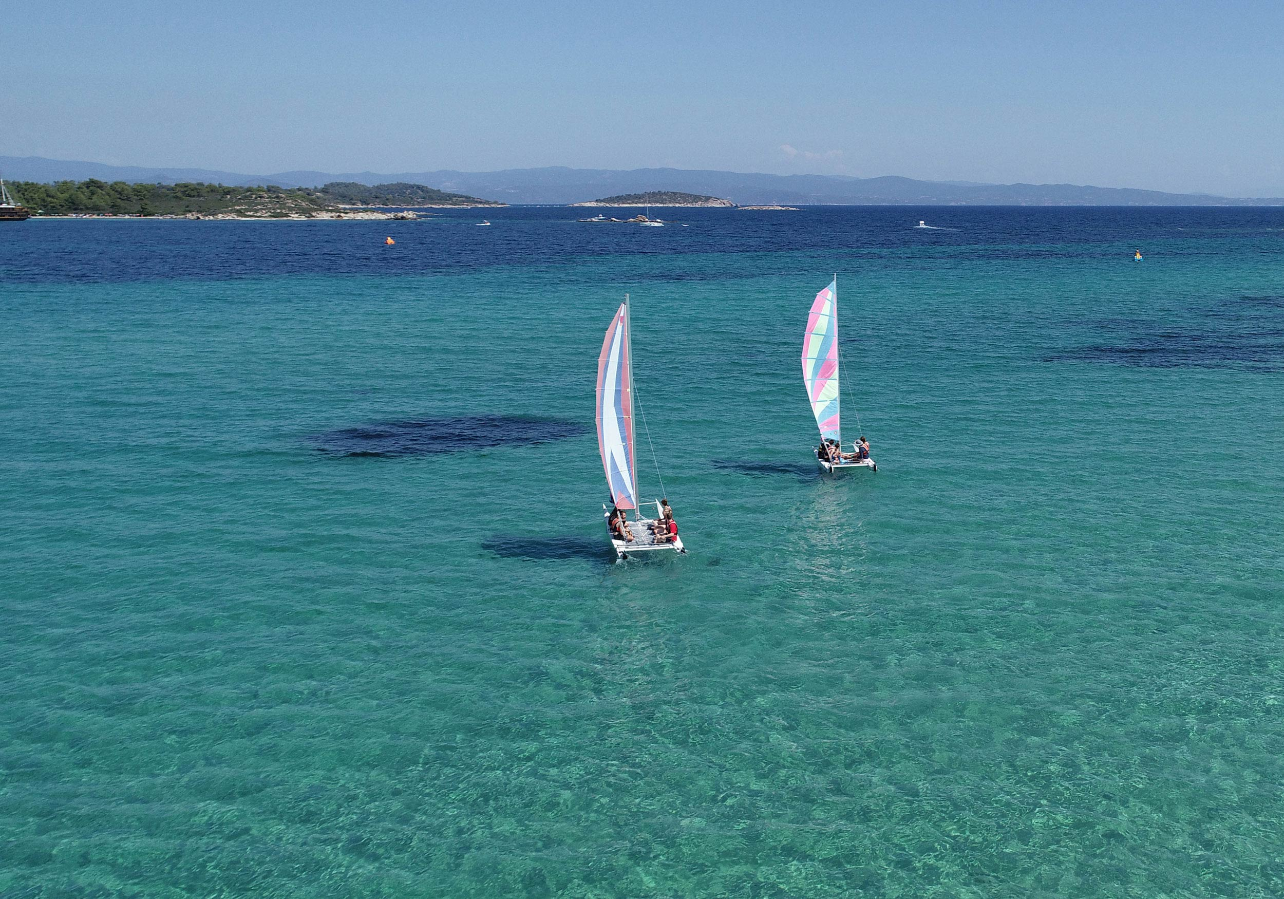 Two catamarans sailing in the blue sea