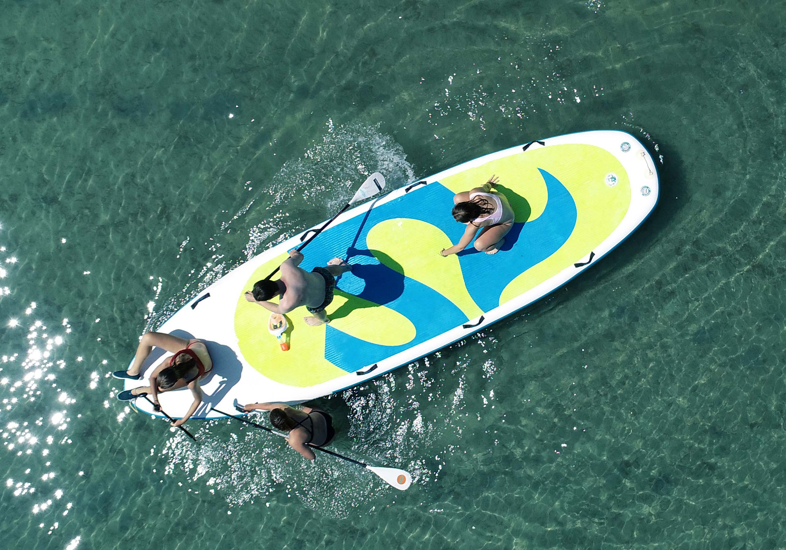 Four people paddling on a mega stand-up board