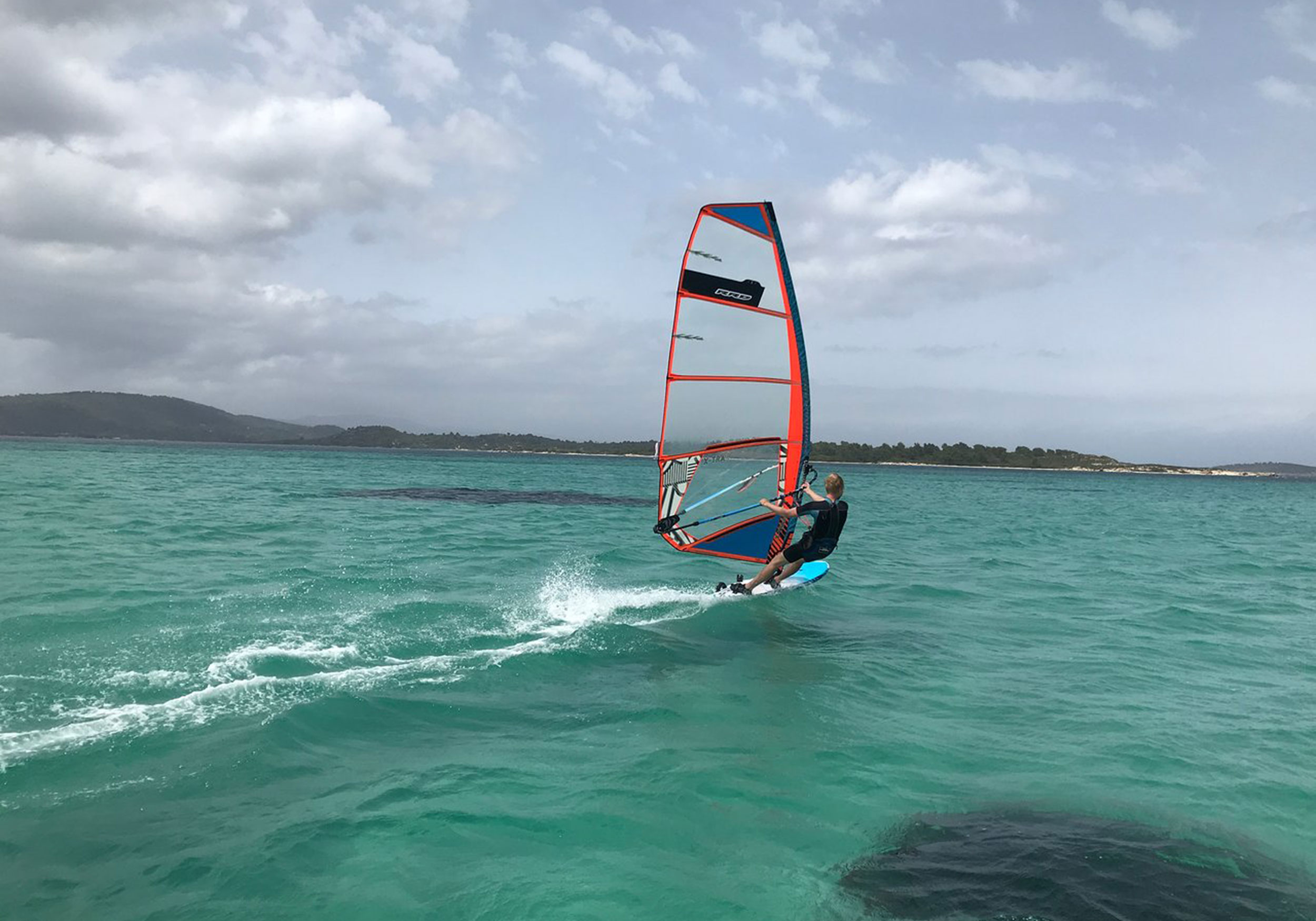 Person windsurfing on a windy day