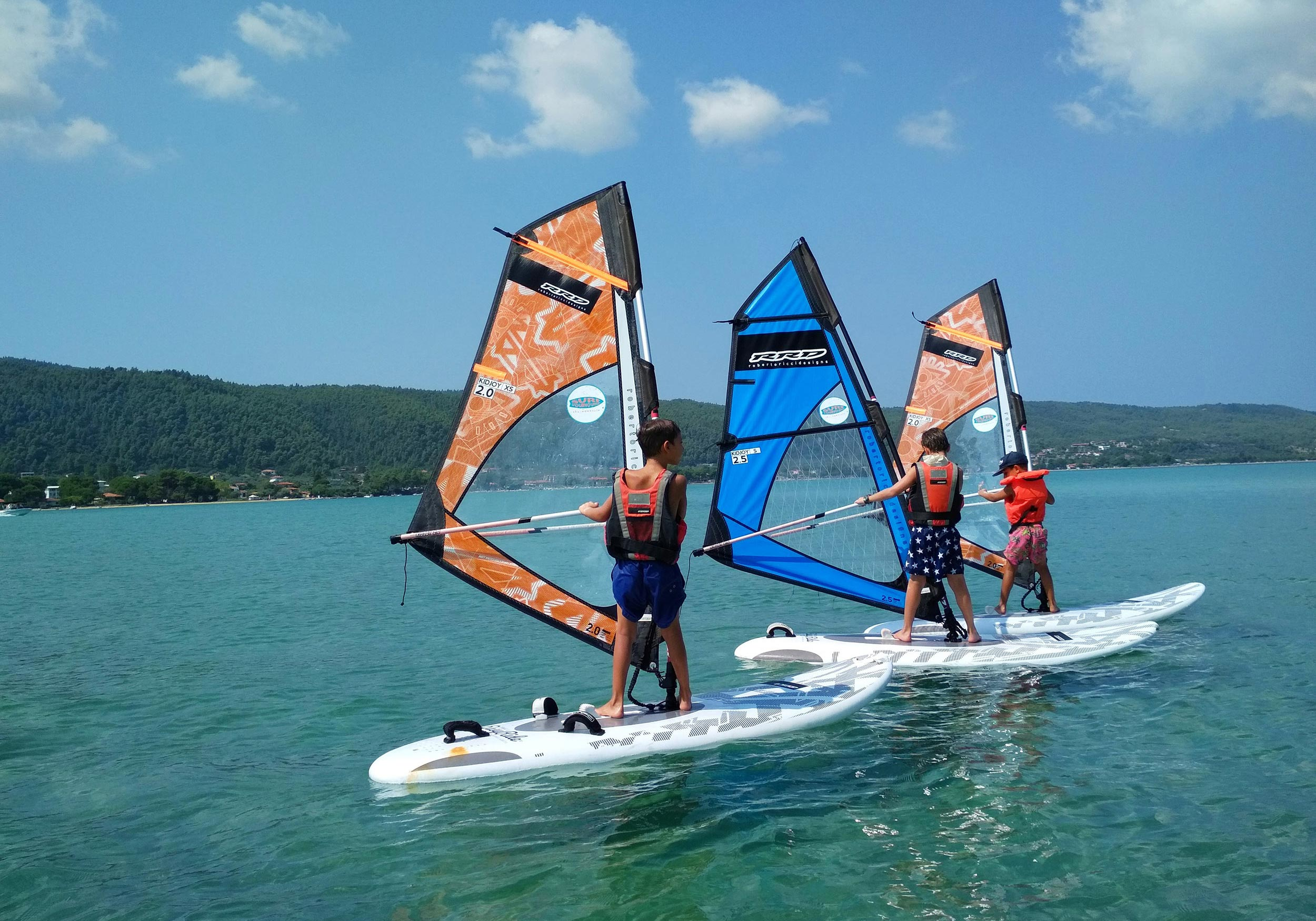 Three children learning to windsurf