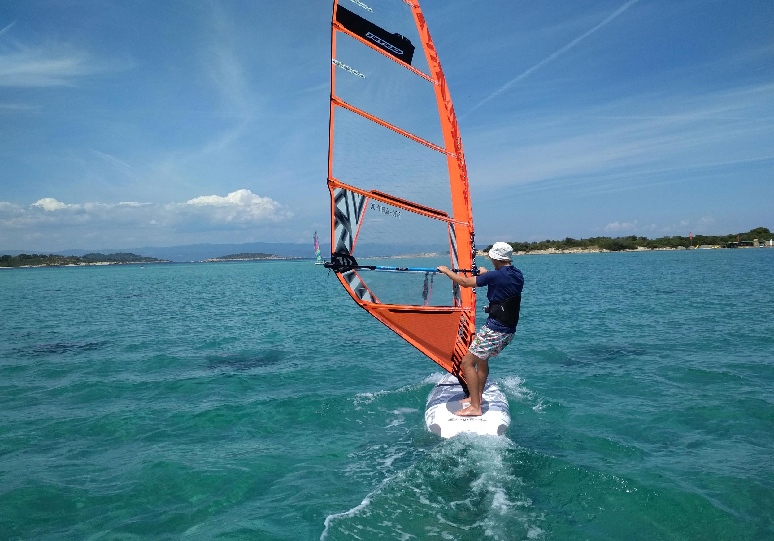 An adult windsurfing in the blue sea