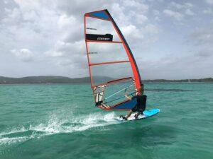 Ein Erwachsener beim windsurfen an einem windigen Tag