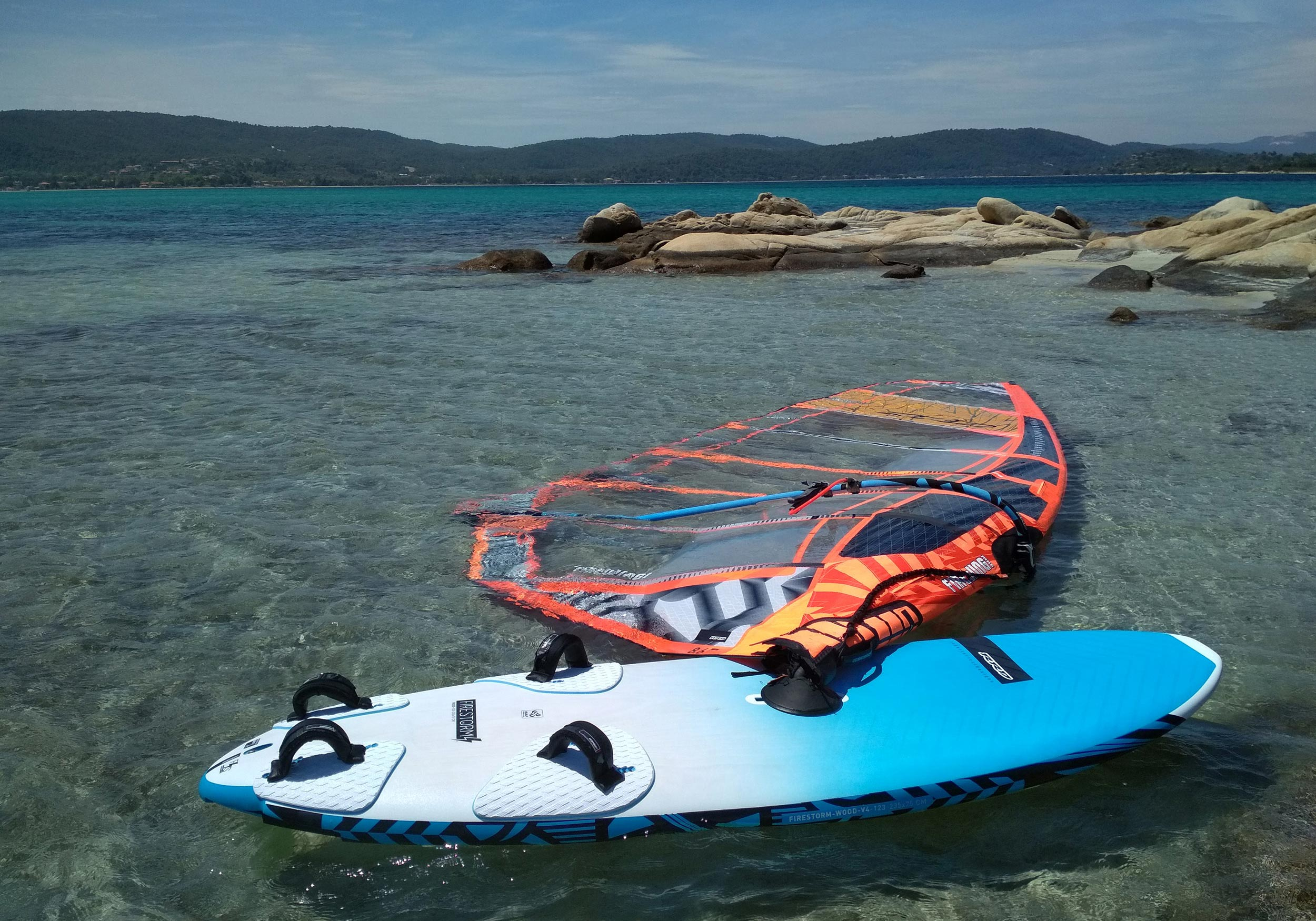 Windsurf board and sail in water.