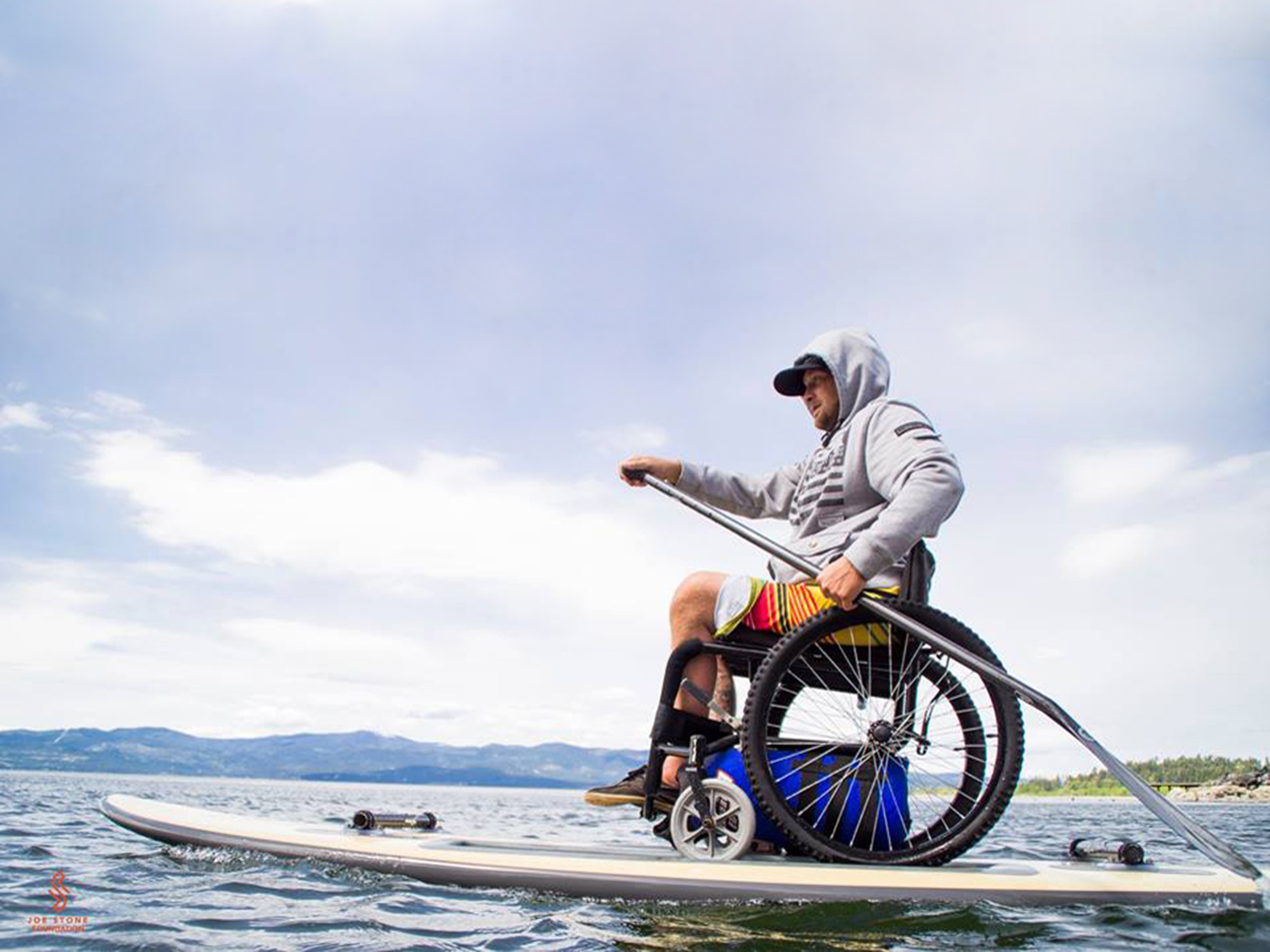 Disabled person paddling on a board