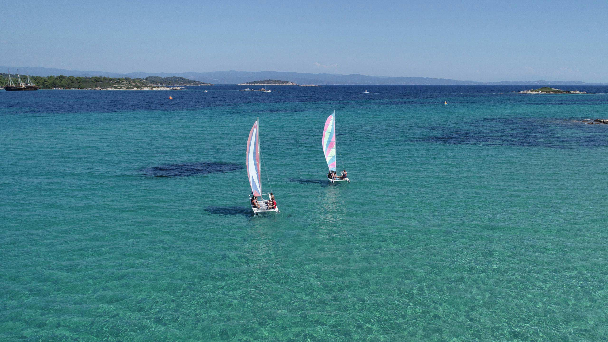 Two catamarans sailing in blue waters