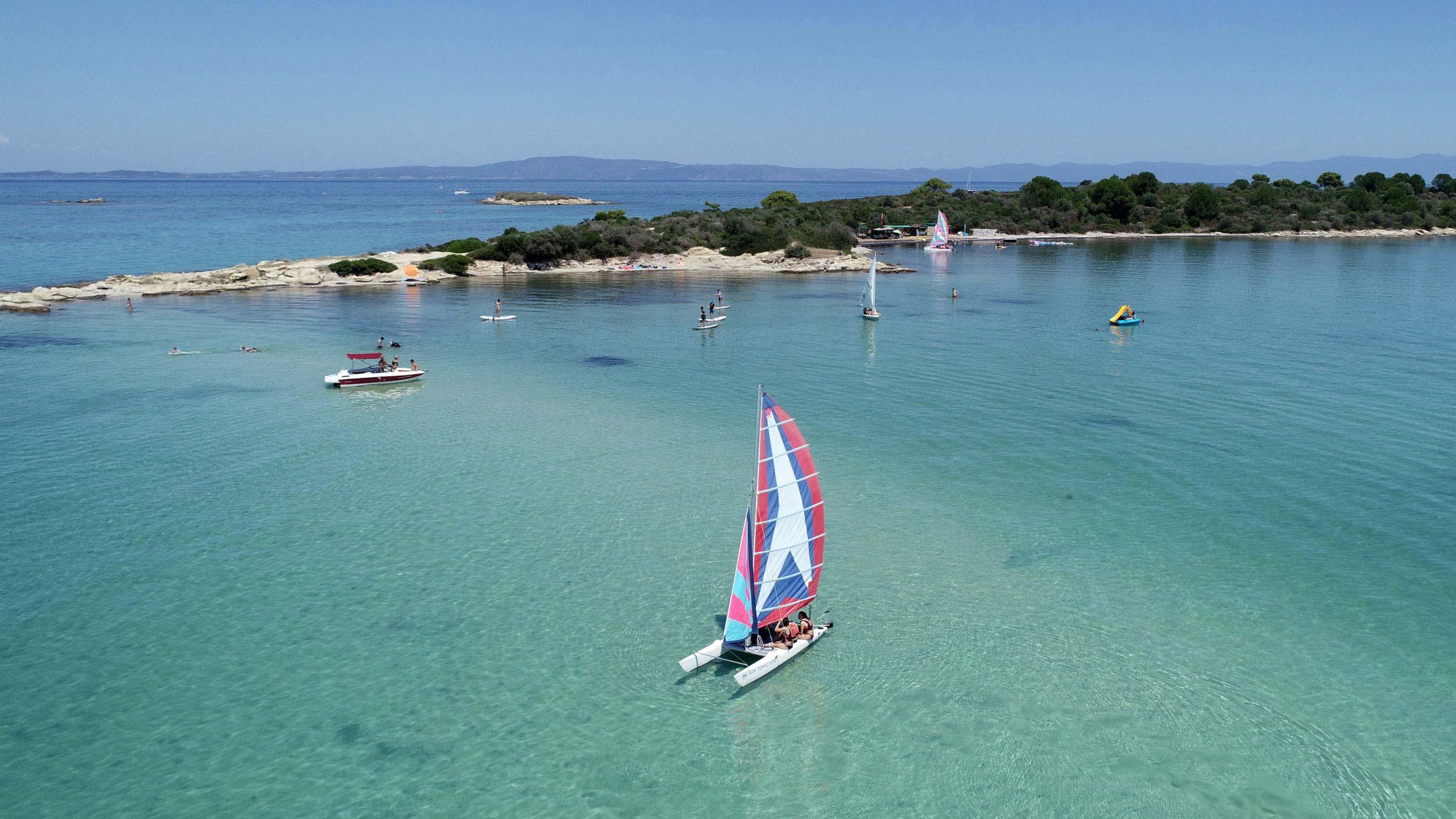Καταμαράν, dinghy και σανίδες stand up πλέοντας σε γαλάζια ρηχά νερά